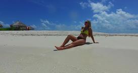 v09998 beautiful young girl in bikini sunbathing and relaxing by the aqua blue Footage