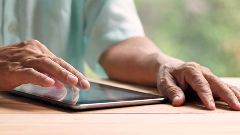 old man touch tablet screen with right hand Filmmaterial