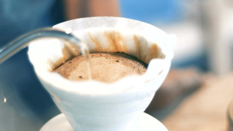 barista pouring hot water on brown coffee ground through... Stock Video Footage