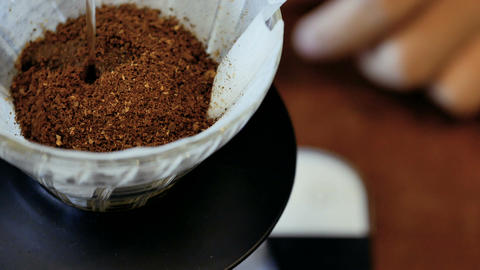barista pouring hot water from kettle on brown coffee through drip filter Live Action