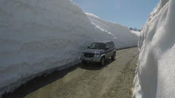 Off-road auto driving on highlands road in snow tunnel surrounded by high ビデオ