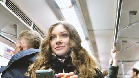 Young beautiful girl with a smartphone in the hands of rides on the subway Filmmaterial