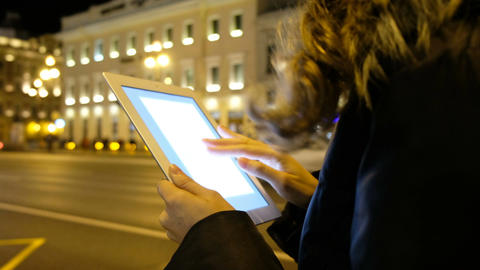 Closeup of a girl looking for information on the tablet in the evening city Archivo