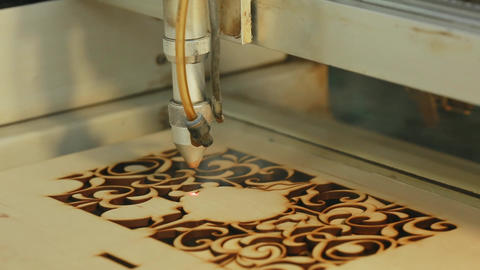 Machine for laser cutting wood close up cuts chipboard and the smoke appears Footage