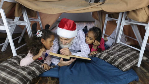 Grandpa in santa hat reading a book with kids 画像