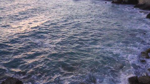 Sea bay at sunset with waves crashing on stony shore. Slow motion Footage
