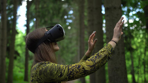 Woman tries to catch virtual objects playing with VR headsetin a forest Live Action