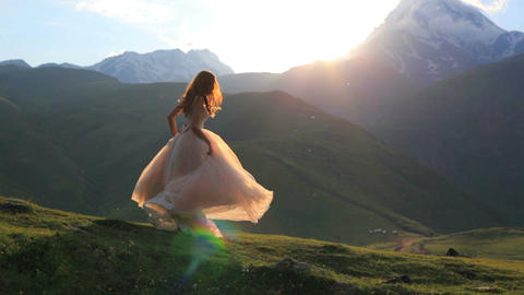 Girl in a beautiful dress on a background of mountains and sunset 影片素材