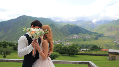 groom and bride closed with a bouquet during the kiss. Georgia Kazbegi Live Action