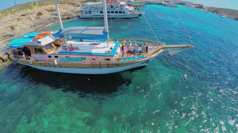 Yachts with tourists stand near a picturesque sea shore. Aerial view. Malta Footage