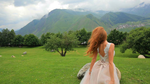 Gorgeous bride blonde posing while looking at mountains. Attractive girl on a Footage