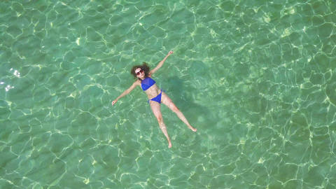 Relaxed beautiful girl lies on her back in the summer sea Footage