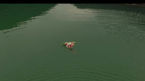 Aerial view of bouquet of roses swims along the green river water. View from Footage