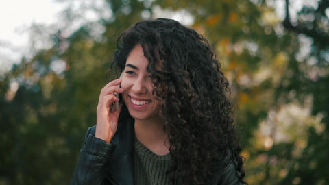 girl with curly hair talking on the phone Footage