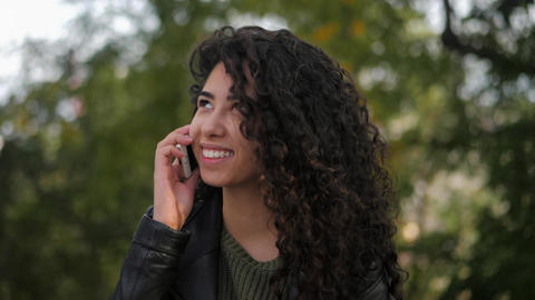 Hispanic girl with curly hair talking on the phone Footage