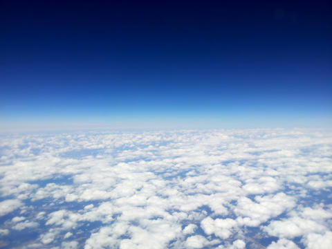 top view of white clouds from a airplane, on a background of the clear blue sky Foto