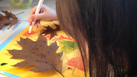 Little girl draws and paints details of the autumn application Footage