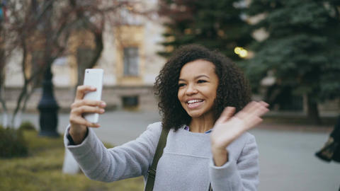 Cheerful mixed race student girl talking at video call with smartphone near Footage