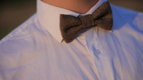 Portrait of a young man in a white shirt and a bow tie GIF