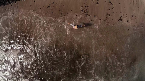 romantic girl goes into the sea. View from above. Aerial photography Footage