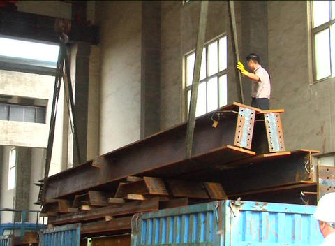 Steel girders unloaded off truck in factory Stock Video Footage