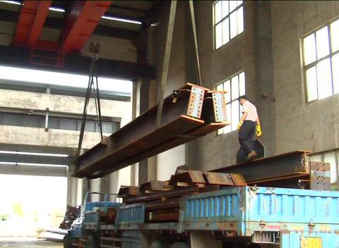Steel girders unloaded off truck in factory Stock Video Footage