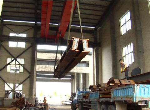 Steel girders unloaded off truck in factory Footage