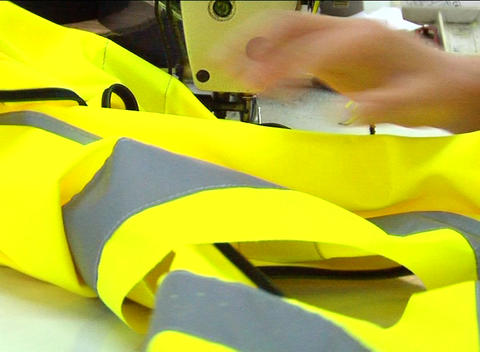 Factory worker's hands sewing jacket Stock Video Footage