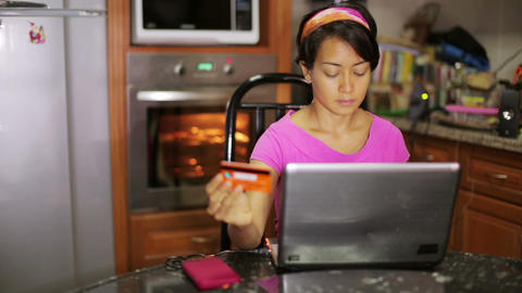 Woman shopping online in kitchen Footage