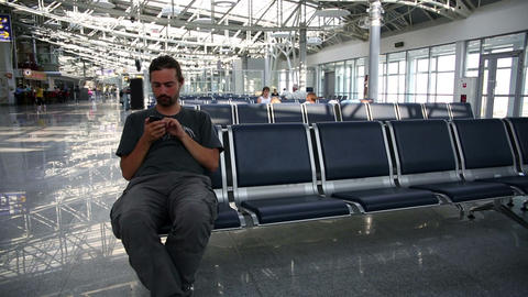 using mobile phone at airport Stock Video Footage
