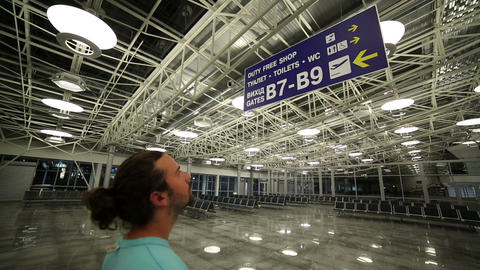 Man looking billboard in airport Stock Video Footage