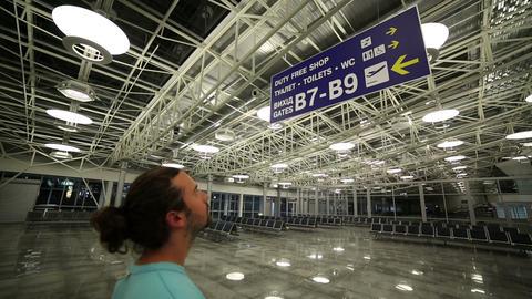 Man looking billboard in airport Stock Video Footage