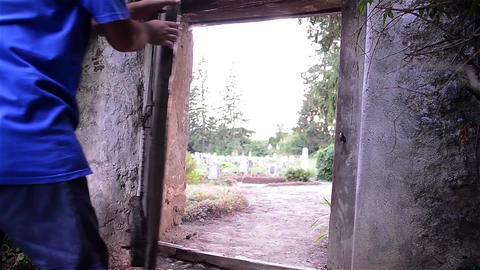 Man opens an old wooden gate and out into the cemetery next to the church Footage