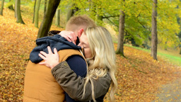 Man surprises woman - young model couple in love - autumn park(nature) - happy c Footage