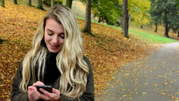 woman on phone (write message) - woman smiles (happy) - woman in autumn park (na Footage