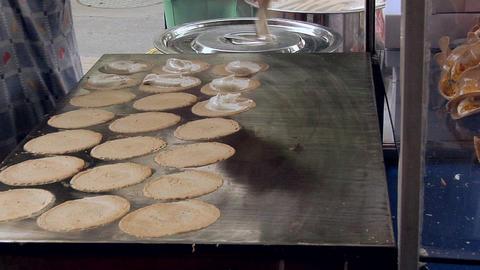 The making of Kanum Bueng, (Coconut Crepes) by a Sidewalk Vendor, Bangkok Footage