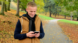 man on phone (write message) - man smiles (happy) - man in autumn park (nature) Footage
