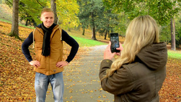 young model couple in love - autumn park(nature) - woman photographing man with  Footage