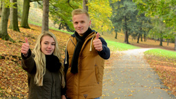 young model couple in love - autumn park(nature) - couple show thumbs on agreeme Footage