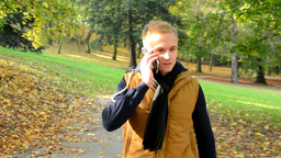 man on the phone (man calling by smartphone) - man walking in autumn park - man  Footage