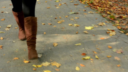 woman walking in autumn park - shot on feet - pavement with leaves Footage