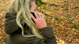 woman on the phone (woman calling by smartphone) - woman walking in autumn park  Footage