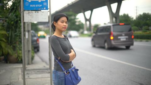 Young Asian Woman waiting at bus stop in Bangkok Footage