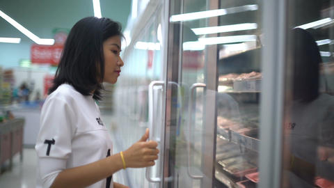 Asian Girl taking meat out from refrigerator in hypermarket Footage