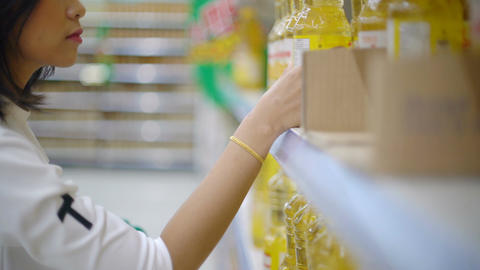 Unrecognizable Woman buying vegetable oil in supermarket Live Action