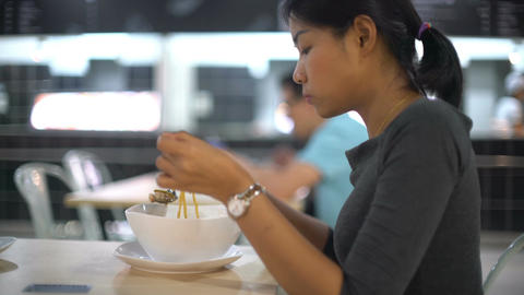 Young Asian Lady eating Thai noodle soup in cafe Live Action
