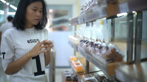 Pretty Asian Woman selecting bakery products in grocery store Footage