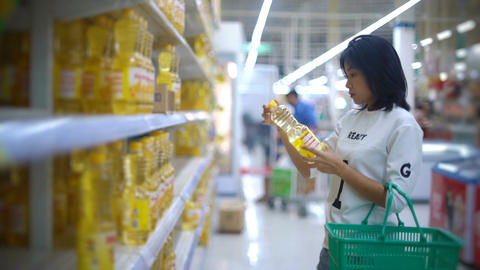 Beautiful Asian Girl taking vegetable oil in hypermarket Footage