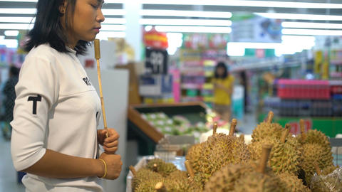 Pretty Thai Woman selects durian fruit in grocery store Footage