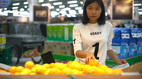 Young Asian Woman choosing oranges in grocery store ビデオ